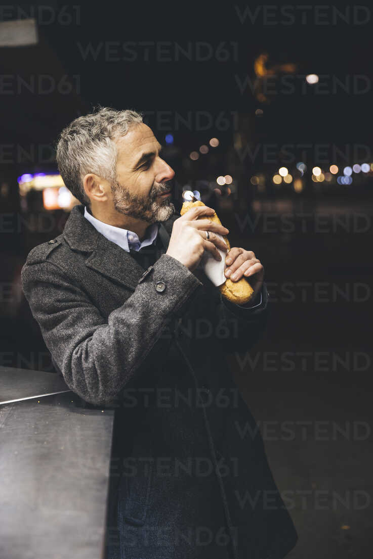 Austria, Vienna, man with Cheese Carniolan sausage at sausage booth by night - AIF000209 - AustrianImages/Westend61
