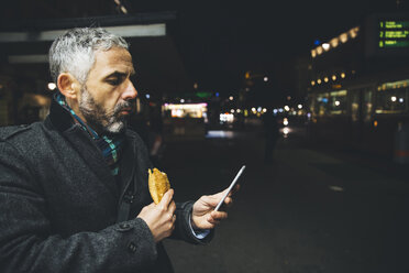 Austria, Vienna, man with Cheese Carniolan sausage looking at his smartphone by night - AIF000212