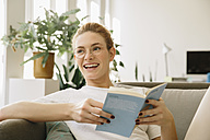 Young woman at home, looking up from her book, laughing - MFF002577