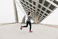 Spain, Barcelona, jogging woman under solar plant - EBSF001205