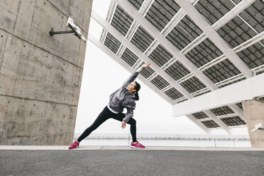 Spain, Barcelona, female jogger, stretching excersice under solar plant - EBSF001211