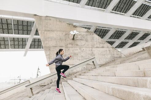 Spain, Barcelona, jogging woman under solar plant - EBSF001214