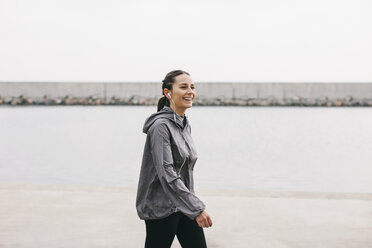 Spain, Barcelona, jogging woman with headphones at harbour - EBSF001217