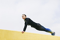 Spain, Barcelona, female jogger on yellow wall, pushup - EBSF001220