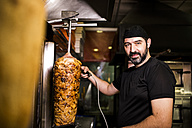 Bearded man preparing kebap meat in snack bar - JASF000337
