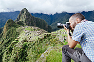 Peru, man taking pictures of Machu Picchu citadel and Huayna Picchu mountain - GEMF000624