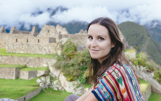 Peru, smiling woman in Machu Picchu citadel with Huayna Picchu mountain in the background - GEMF000627