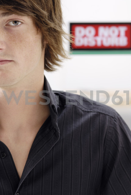 Portrait of teenage boy with 'Do not disturb' sign in the background, close-up - GUFF000180