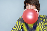 Teenage boy blowing red balloon in front of blue background - GUFF000183
