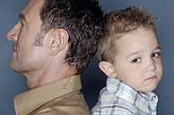 Sad little boy sitting back to back with his father - GUFF000189