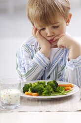 Portrait of little blond boy looking at plate with vegetables - GUFF000204