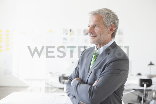 Confident businessman in office thinking - RBF003989