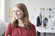 Smiling young woman in office looking away - RBF004019