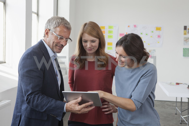 Smiling usinessman and two women in office looking at digital tablet - RBF004025