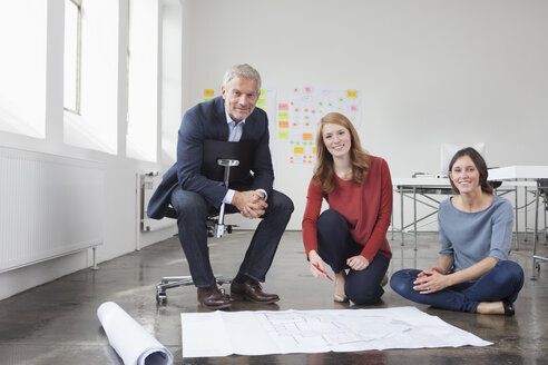 Portrait of smiling businessman and two women in office with construction plan - RBF004031
