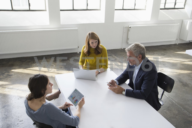 Businessman and two women in conference room having a meeting - RBF004043
