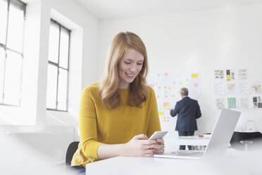 Smiling young woman in office at desk with laptop and cell phone - RBF004046