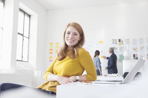 Smiling young woman in office at desk - RBF004049