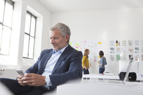 Businessman in office at desk looking at cell phone - RBF004055