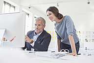 Businessman and woman in office working on computer together - RBF004058