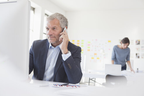 Businessman in office at desk on cell phone - RBF004061