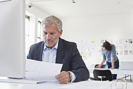Businessman in office at desk looking at paper - RBF004064