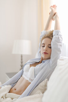 Portrait of blond woman sitting in bed stretching - SHKF000433