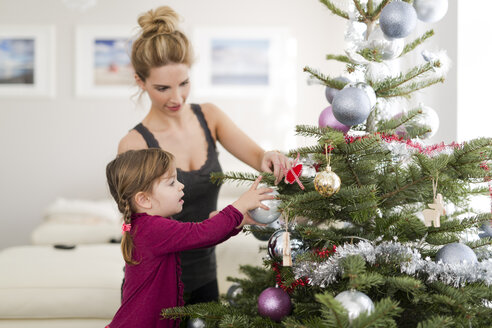 Little girl decorating Christmas tree with her mother in the living room - SHKF000436