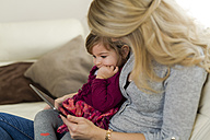 Little girl sitting on her mother's lap looking at digital tablet - SHKF000439