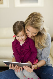 Mother and her little daughter looking at digital tablet - SHKF000442