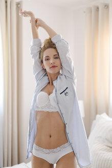Portrait of blond woman wearing underwear and pyjama jacket - SHKF000454