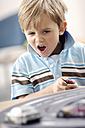 Portrait of blond little boy playing with Carrera - GUFF000218