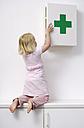 Blond little girl opening medicine cabinet - GUFF000221