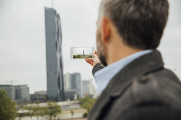 Austria, Vienna, businessman taking a picture of DC Towers with his smartphone - AIF000214