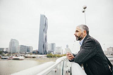 Austria, Vienna, businessman with smartphone standing on Reichsbruecke looking at distance - AIF000217