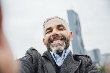 Austria, Vienna, portrait of businessman taking a selfie with his smartphone - AIF000220