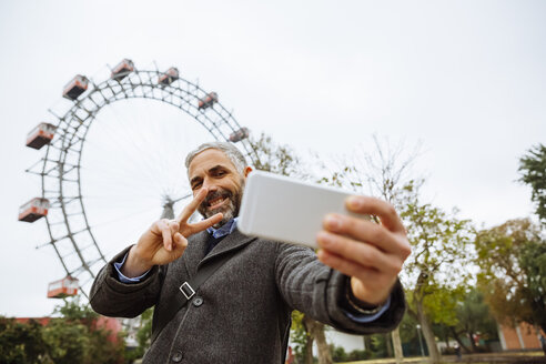 Austria, Vienna, portrait of smiling businessman taking a selfie at Prater - AIF000225