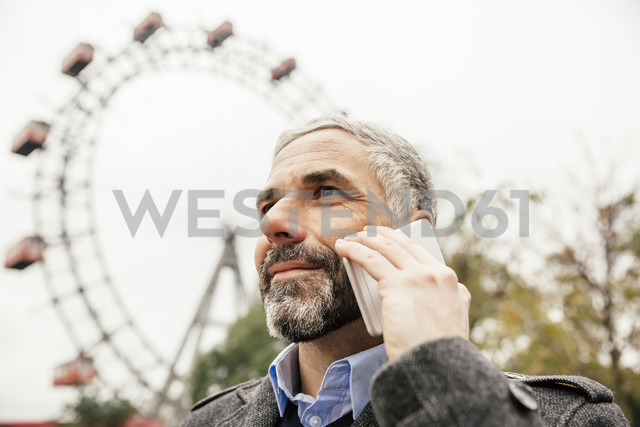 Austria, Vienna, portrait of smiling businessman telephoning with smartphone at Prater - AIF000228
