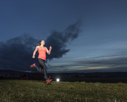 Young woman jogging on a meadow at sunset - STSF000991