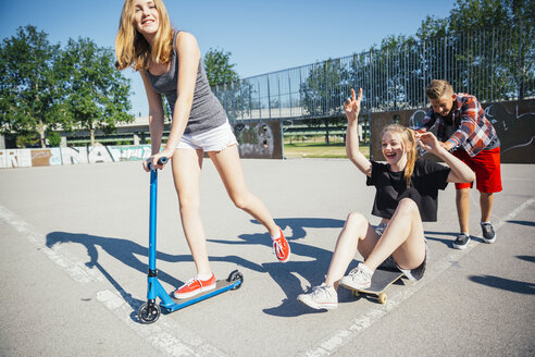 Three playful teenage friends with scooter and skateboard - AIF000257