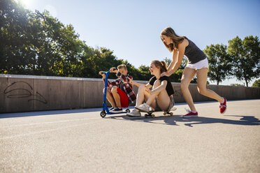 Three playful teenage friends with scooter and skateboard - AIF000263