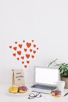 Still life with laptop, donuts, Valentine's day present and hearts on wall - EBSF001230