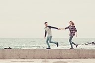 Young couple walking hand in hand by the sea - SIPF000024