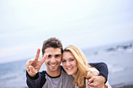Happy young couple embracing and making victory sign - SIPF000027
