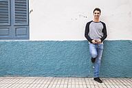 Smiling young man leaning against a wall - SIPF000030