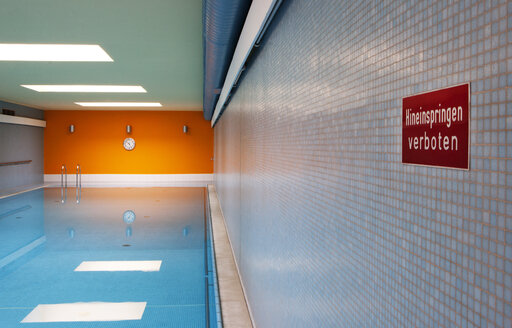 Empty indoor swimming pool with sign - WWF003907