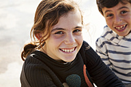 Spain, Barcelona, portrait of happy girl with brother watching in the background - VABF000038