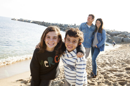 Spain, Barcelona, portrait of happy brother and sister on the beach with their parents in the background - VABF000047