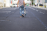 Back view of boy carrying his skateboard on a street - SIPF000042