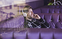 Young man sitting in a lounge bar hearing music with headphones - FMKF002240